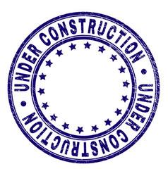 grunge textured under construction round stamp vector image