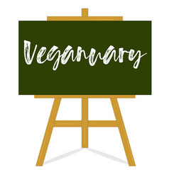 veganuary message blackboard on a wooden easel vector image