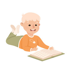 Smiling blond boy lying on floor and reading book vector
