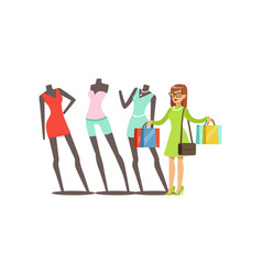 young woman choosing clothes on mannequins in a vector image