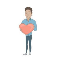 Hispanic businessman holding a big red heart vector
