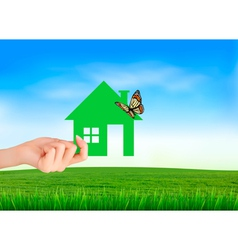 The house in hand on green natural background vector image vector image