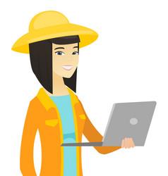 Young asian farmer using a laptop vector