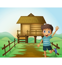 A boy waving his hand in front of a nipa hut vector image