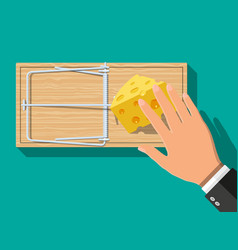 Wooden mouse trap with cheese and hand vector