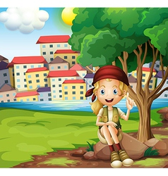 A girl sitting above the rock under the tree vector image