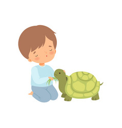 cute boy feeding turtle with grass kid vector image