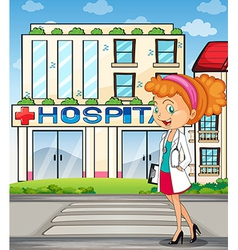 A pretty doctor standing in front of the hospital vector image
