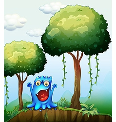 A smiling blue monster at the forest near the vector image vector image