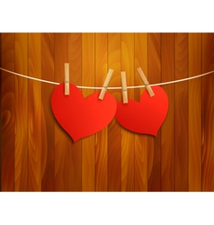 Two red loving hearts hanging on a rope vector