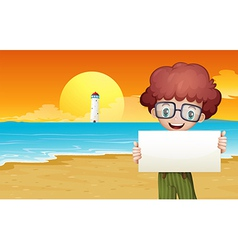 A boy at the beach holding an empty signage vector image