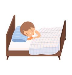Cute smiling boy sleeping in his bed under blanket vector