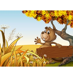 A beaver playing under the tree while holding an vector image vector image