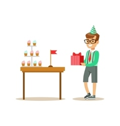 Boy holding a present standing next to table vector