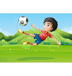 A young boy playing football at the field vector image