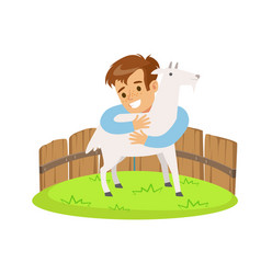 Happy little boy embracing a white goat in a mini vector