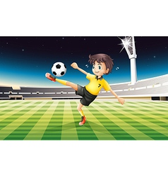 A boy in his yellow uniform playing soccer at the vector image