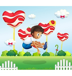 A boy jumping in the field with giant lollipops vector