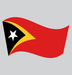 Flag of east timor waving on gray background vector