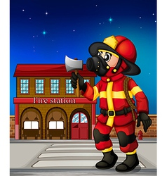 A fireman holding an ax outside the fire station vector image vector image