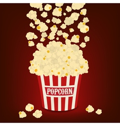 Popcorn falling in the striped popcorn bag vector image