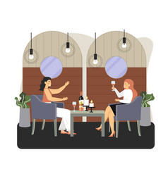 two young women sitting at table and drinking wine vector image