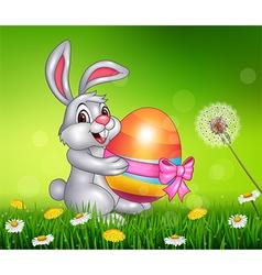 Cute little bunny holding Easter egg on grass vector