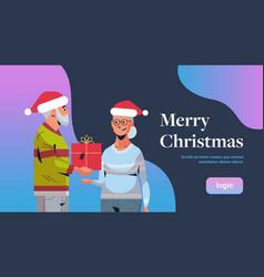 senior man in santa hat giving present gift box to vector image