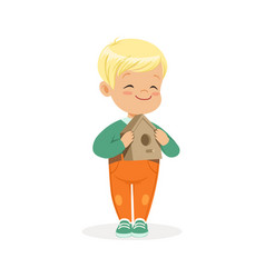 cute smiling little boy standing and holding vector image vector image