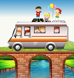 Children riding on camper van over the bridge vector image