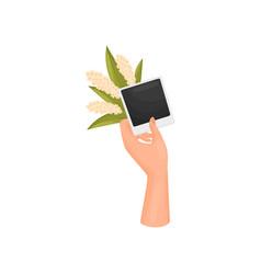 Hand holds a photo card a poloroid and a vector