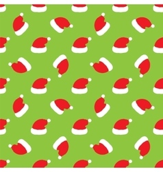 Red Santa hats on green background vector image