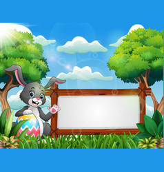 easter bunny holding a large egg near a blank sign vector image