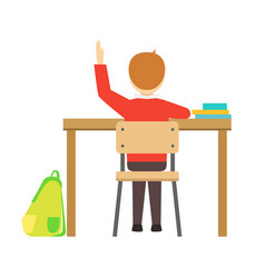 Boy raising hand sitting at his desk in classroom vector