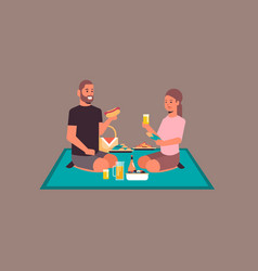 Happy couple sitting on blanket eating hot dogs vector