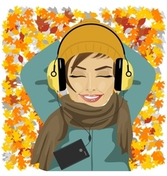 woman listening to music lying on autumn leaves vector image