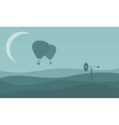 Silhouette of air balloon with windmill vector