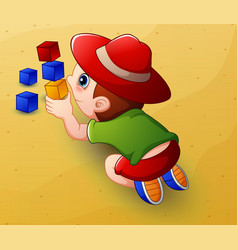 Cartoon little boy playing with cubes toys in sand vector