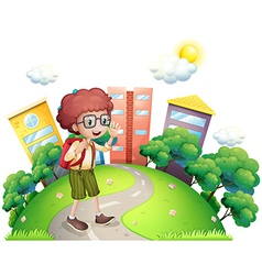 A schoolboy waving while walking at the road vector