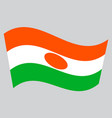flag of niger waving on gray background vector image vector image