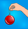 hand with christmas tree toy pop art vector image