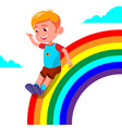 happy child boy rolling down rainbow vector image
