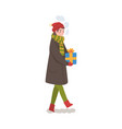 teenage boy in winter clothing walking with gift vector image