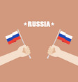hands holding up russia flags vector image vector image