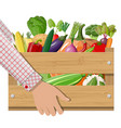 wooden box full of vegetables in hand vector image vector image