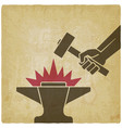 hand with hammer above anvil vintage vector image vector image