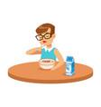 cute boy eating porridge while having breakfast in vector image vector image