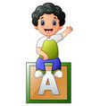 little boy sitting on alphabet cube vector image vector image