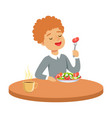 happy redhead boy sitting at the table and eating vector image vector image