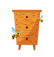 wood hive for bees with bees around it vector image